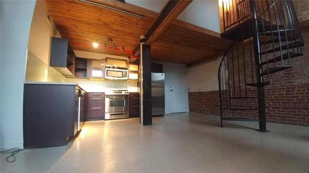 2 Story Industrial Brick Loft W/Spiral Staircase Leading To Upstairs Level  At The